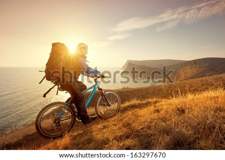 cyclist on a mountain bike travels around the beautiful landscape stock photo