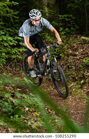 cyclist on a mountainbike in a downhill - stock photo