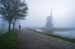 Cyclist on an old countryroad in the Netherlands during a foggy  morning.