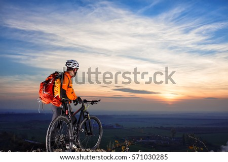 cyclist on mountain-bike at sunset, cyclist on the background of beautiful sunset. cyclist with white helmet and red backpack. beautiful landscape. back view. #571030285