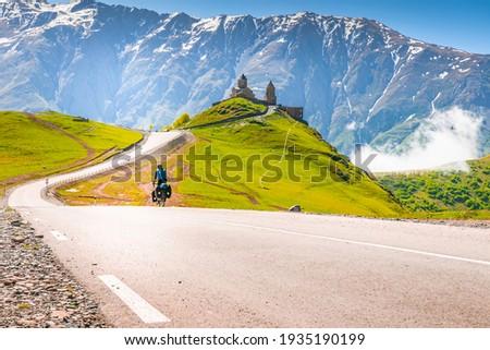 Cyclist on the road going towards Gergeti trinity monastery in Georgia, Caucasus. Traveler on bicycle,