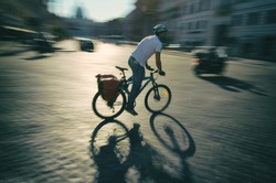 Cyclist passes by in a blur along the traditional cobblestone streets of Rome Italy
