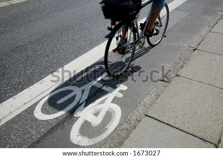 Cyclist passing by on urban cycle path.