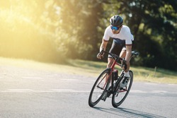 Cyclist pedaling on a racing bike outdoors in sun set .The image of cyclist in motion on the background in the evening.