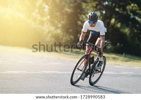 Cyclist pedaling on a racing bike outdoors in sun set .The image of cyclist in motion on the background in the evening. Foto d'archivio ©