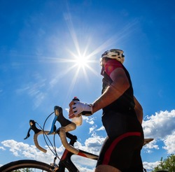 Cyclist resting and drinking isotonic drink. Backlight, sunny summer day.