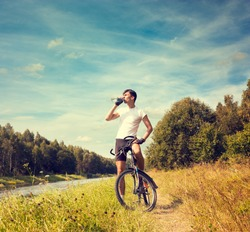Cyclist Resting and Drinking Water at Summer River Background. Healthy Lifestyle Concept. Copy Space.