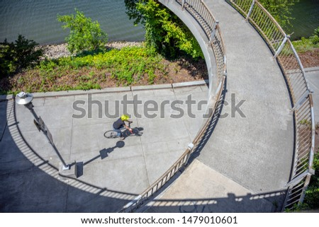 Cyclist rides along a path along a river under an oval bridge. The use of a bicycle as the main transport for many enthusiasts has grown from a hobby into vital necessity