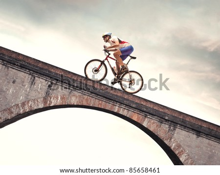 Cyclist riding bike on a bridge - stock photo