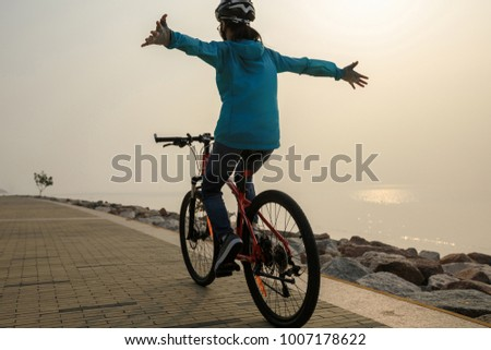 cyclist riding bike with arms outstretched in the coasts sunrise sunshine wellness concept