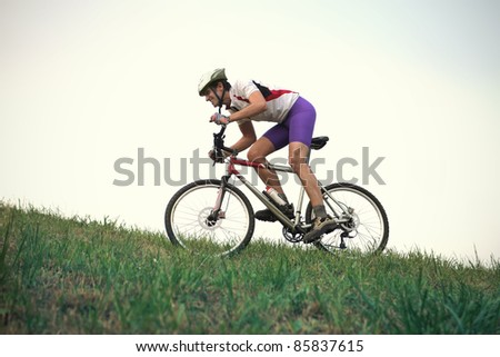 Cyclist riding on a green meadow