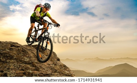 Cyclist Riding the Bike Down the Rock at Sunrise in the Beautiful Mountains on the Background. Extreme Sport and Enduro Biking Concept.