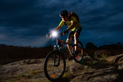 Cyclist Riding the Mountain Bike on the Rocky Trail at Night. Extreme Sport and Enduro Biking Concept.