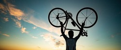 cyclist silhoutte with bicycle raised to sky race and victory concept