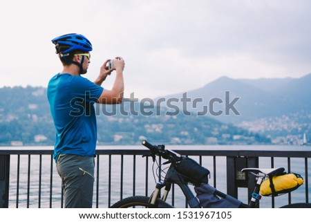 Cyclist taking pictures with smart phone. Caucasian man in bike helmet taking photo of landscape. Outdoor activity. Tourist makes photo of Lake Como in Italy. travel people lifestyle.