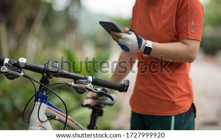 Cyclist use smartphone when riding mountain bike on forest trail Stock photo ©