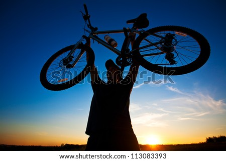 cyclist with a bicycle in his hands silhouette on a blue sky