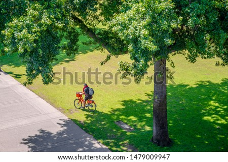Cyclist with a bicycle resting on the grass in a large meadow of a city park. The use of a bicycle as the main transport for many enthusiasts has grown from a hobby into vital necessity