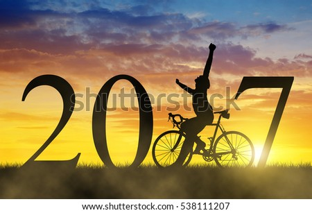 Cyclist with bicycle at sunset. Forward to the New Year 2017 #538111207