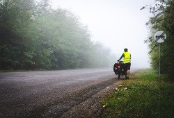 Cyclist with reflective vest and lighs on is walking down the road to the fog in nature. Bicycle touring in bad  weather conditions and bad visability.