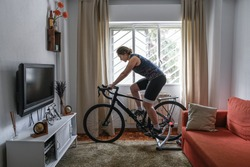 Cyclist woman. She is training on the bike with a smart trainer at home. Stay fit and active while at home.