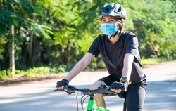 Cyclist woman wearing a mask while riding a bicycle outdoor for protect and prevent the spread of virus.