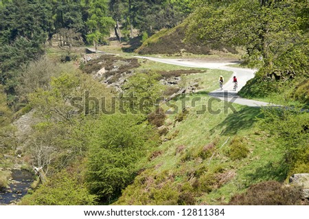 cyclists cycling along road in the goyt valley the peak district national park derbyshire england uk