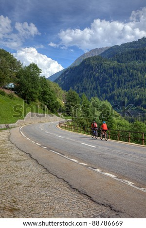 Cyclists on road among swiss alps, Europe.