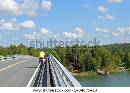 Cyclists on the bridge. Beautiful summer day. Rear view. #1484895410