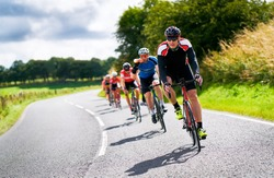 Cyclists racing on country roads on a sunny day in the UK.