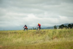 Cyclists riding the Otago Central Rail Trail under the cloudy sky towards Middlemarch, South Island, New Zealand