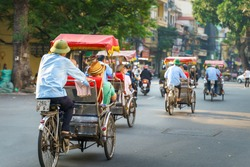 Cyclo driver taking tourist visiting old quarter on street in Hanoi