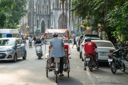 Cyclo (pedicab) on Hanoi street at early morning with St. Joseph Cathedral on background