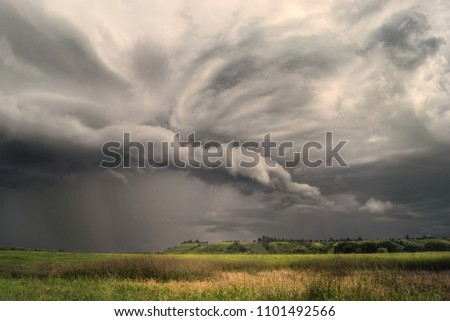 Cyclone storm over fields and meadows approaches the hilly valley. Rainy cloudy day.