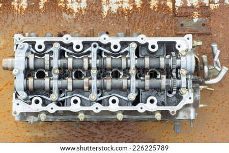 cylinder head and bent shaft on the background of rusty metal, broken engine car parts