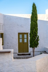 Cypress tall tree at cobblestone yard, whitewashed stonewalls traditional house background, closed wooden door and window. Milos island, Plaka Chora, Cyclades Greece. Vertical
