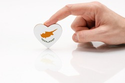 Cyprus flag. Love and respect Cyprus. A man's hand holds a heart in the shape of the Cyprus flag on a white glass surface. The concept of Cypriot patriotism and pride.