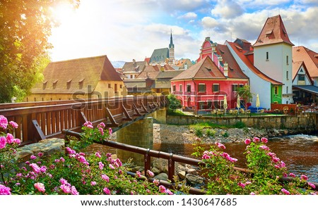 Czech Krumlov, (Cesky Krumlov), Czech Republic. Wooden bridge over river Vltava. Vintage picturesque old town with colorful houses and chapel of church. Rose flowers on bank. Sunny summer day. Stock photo ©