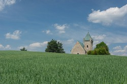 Czech landscape view with crop field and with romanesque church of Archangel Michael. Vitochov village, Czech Republic.