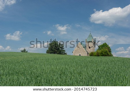 Czech landscape view with crop field and with romanesque church of Archangel Michael. Vitochov village, Czech Republic. Foto stock ©