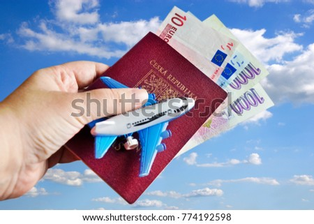 Czech passport - travelling by air - euro and Czech crown money with aircraft modell in the dand against blue sky - Shutterstock ID 774192598