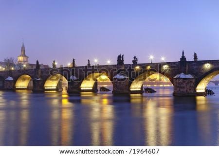 czech republic prague - illuminated charles bridge at dusk in winter