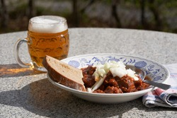 Czech style beef goulash served in deep rustic plate with slice of bread and mug with czech lager beer, on the top of the meal is chopped white onion. Food is served outside in the garden restaurant.