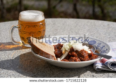 Czech style beef goulash served in deep rustic plate with slice of bread and mug with czech lager beer, on the top of the meal is chopped white onion. Food is served outside in the garden restaurant. Foto stock ©