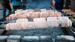 Czech sweet specialty Trdelnik on wooden poles over fire pit in Prague