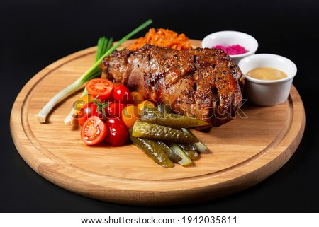 Czech traditional food pork knee veprevo koleno with pickled cucumber and tomatoes and different sauces on the wooden board. pub menu concept. baked meat on black background  Foto stock ©