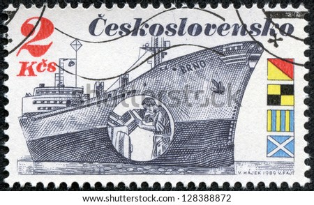 """CZECHOSLOVAKIA - CIRCA 1989: A stamp printed in Czechoslovakia shows the Czech Freighter Brno with inset showing a man peering at radar display. Flags spell """"OLGM"""" in English, circa 1989."""