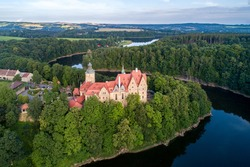 Czocha medieval castle in Lower Silesia in Poland. Built in 13th century  with many later additions. Aerial view in summer, early morning. Kwisa river with artificial lake Lesnianskie and forests