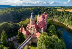 Czocha (Tzchocha) medieval castle in Lower Silesia in Poland. Built in 13th century (the main keep) with many later additions. Aerial view in summer with Kwisa river and tourist boat