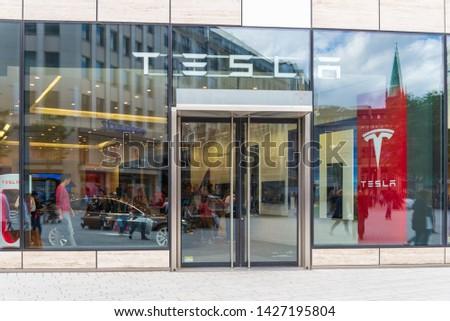 Düsseldrof, Germany - June 2019: Outdoor sunny view in front of exterior glass wall facade and entrance Tesla store at Kö-Bogen shopping mall near Schadowplatz in Düsseldorf, Germany.